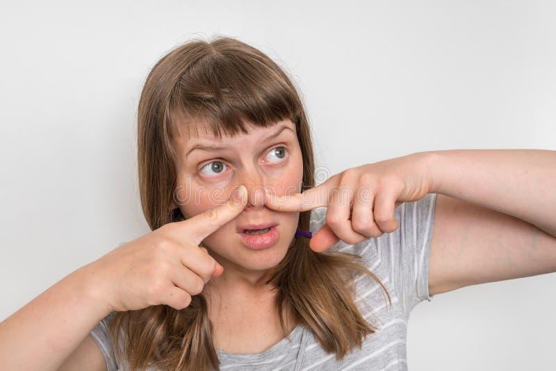 Junge Frau hält ihre Nase - Konzept des schlechten Geruchs lizenzfreie stockfotos