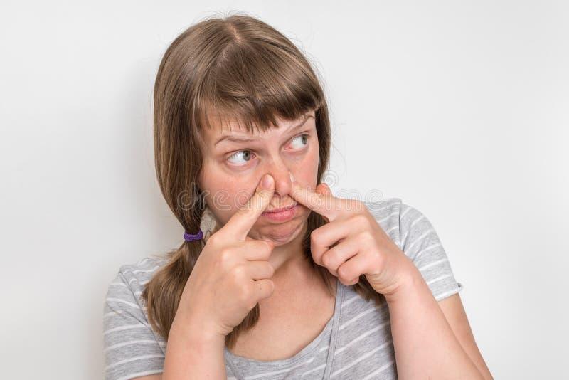 Junge Frau hält ihre Nase - Konzept des schlechten Geruchs stockbild