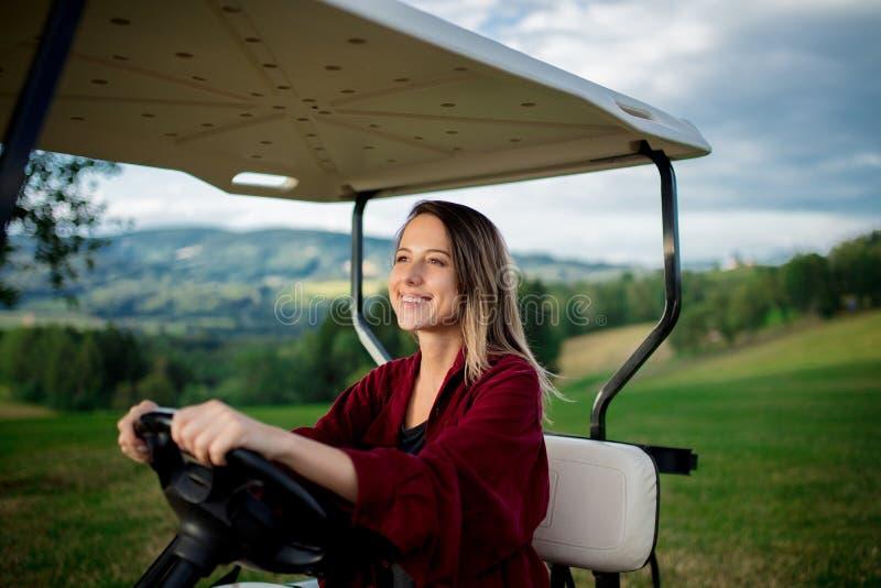 Junge Frau haben einen Spaß mit verwanztem Auto des Golfs auf einem Feld in den Bergen lizenzfreie stockfotografie