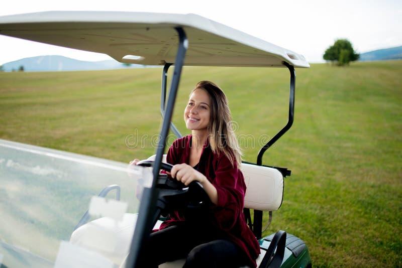 Junge Frau haben einen Spaß mit verwanztem Auto des Golfs auf einem Feld in den Bergen lizenzfreies stockbild