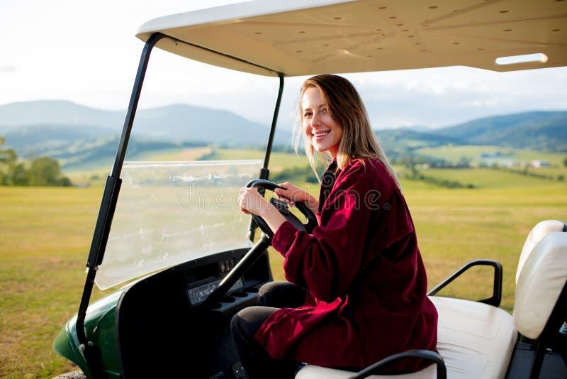 Junge Frau haben einen Spaß mit verwanztem Auto des Golfs auf einem Feld in den Bergen stockfotos