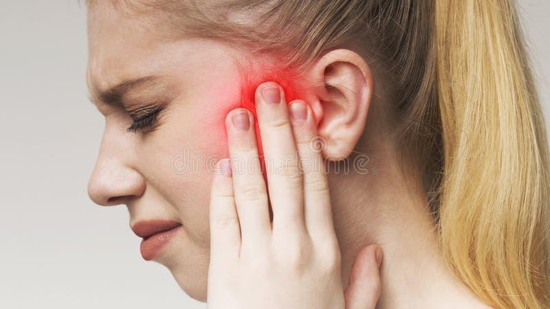 Junge Frau hat das wunde Ohr und leidet unter Mittelohrentzündung stockfoto