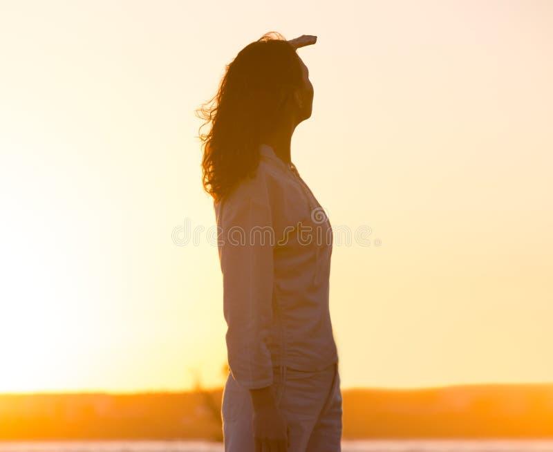 Junge Frau in hellem weit weg schauen des Sonnenuntergangs lizenzfreie stockbilder
