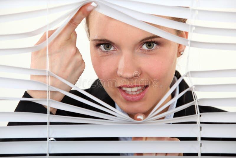 Junge Frau hinter Vorhängen lizenzfreie stockbilder