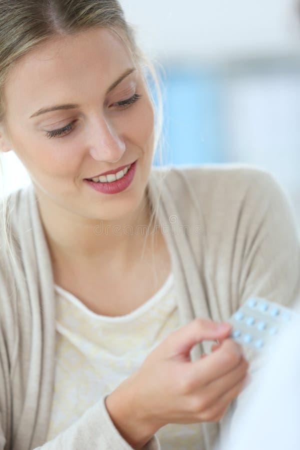 Junge Frau Holding-Pillen stockbild