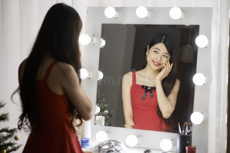 Junge Frau an ihrer Eitelkeit stockbild