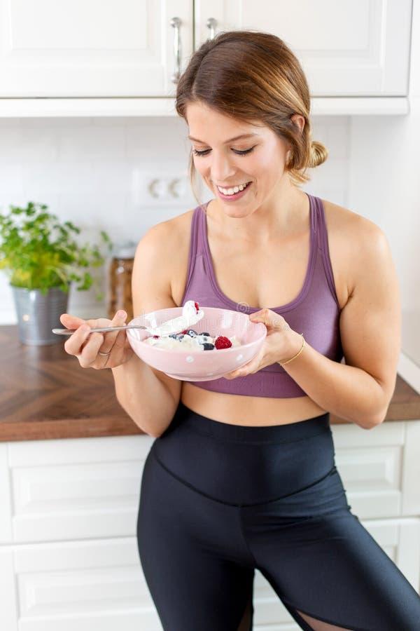 Junge Frau in ihrer Hauptküche Frühstück essend lizenzfreie stockfotografie