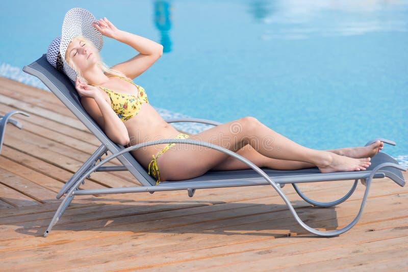 Junge Frau im Badeanzug, der auf Liege Poolside legt lizenzfreies stockfoto