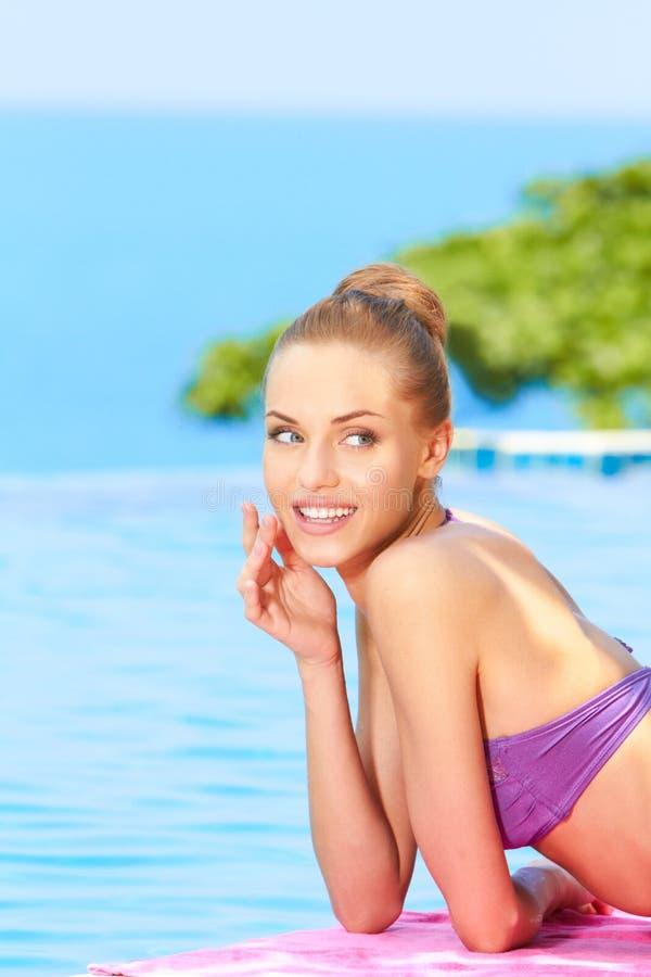 Junge Frau im Badeanzug, der nah an Pool liegt stockfoto