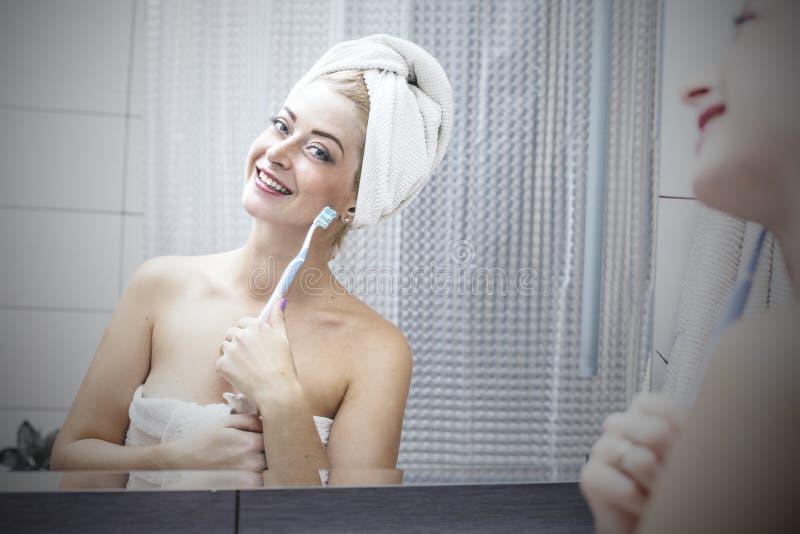 Junge Frau im Badezimmer, das ihre Zähne mit einem Zahnbürstenesprit putzt lizenzfreies stockfoto