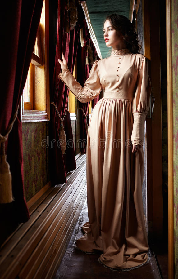 Junge Frau im beige Weinlesekleid des Anfang- des 20. Jahrhundertsdoubles lizenzfreie stockfotografie