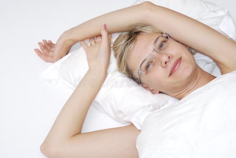 Junge Frau im Bett stockbilder