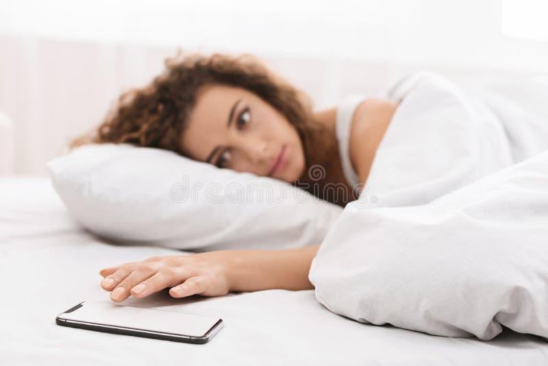 Junge Frau im Bett, das durch Handy aufgeweckt wird stockfotografie