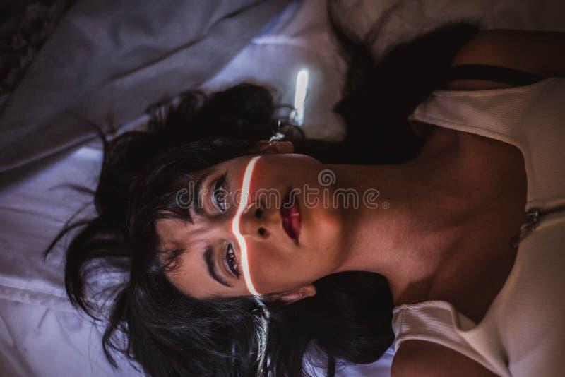 Junge Frau im Bett mit einem Lichtstrahl ihr Gesicht und intensives Anstarren kreuzend lizenzfreies stockfoto