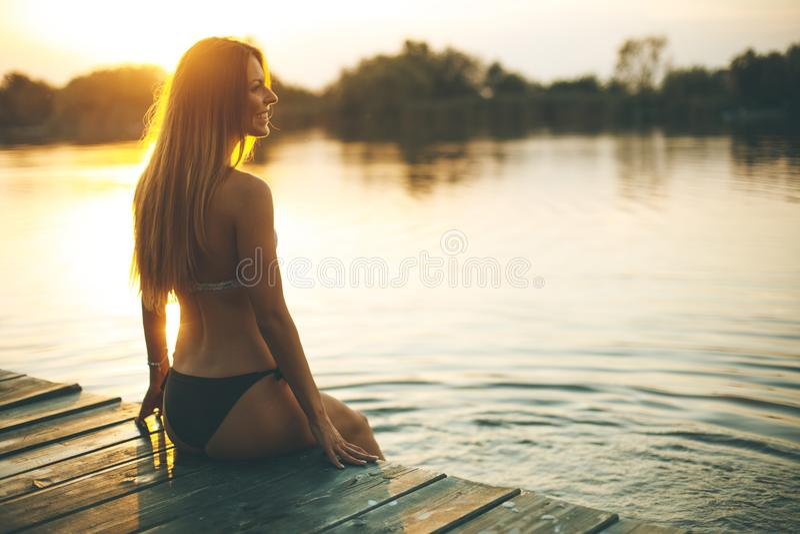 Junge Frau im Bikini auf Pier durch Fluss stockbild