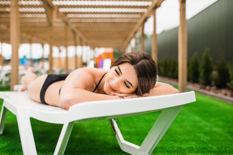 Junge Frau im Bikini, Badeanzug, der auf Liege legt und durch das Pool in Sommerferien ein Sonnenbad nimmt lizenzfreie stockfotografie