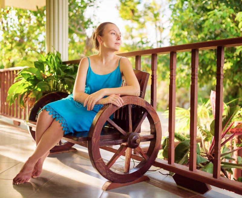 Junge Frau im blauen Kleid, das in der Hausterrasse sich entspannt lizenzfreies stockbild