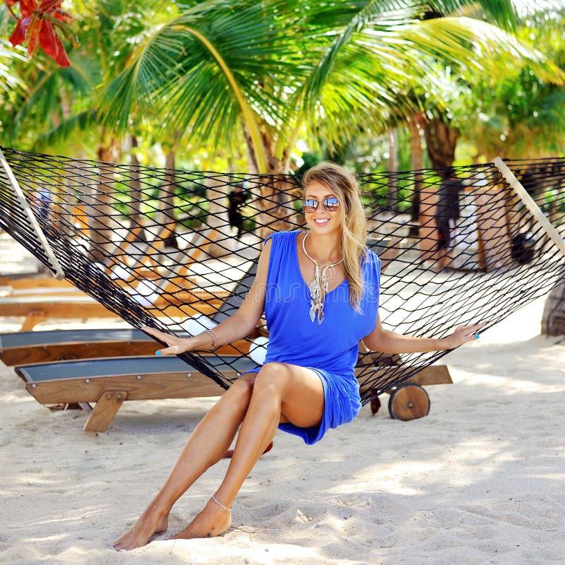Junge Frau im blauen Kleid und in der Sonnenbrille, die in der Hängematte sitzt stockbilder