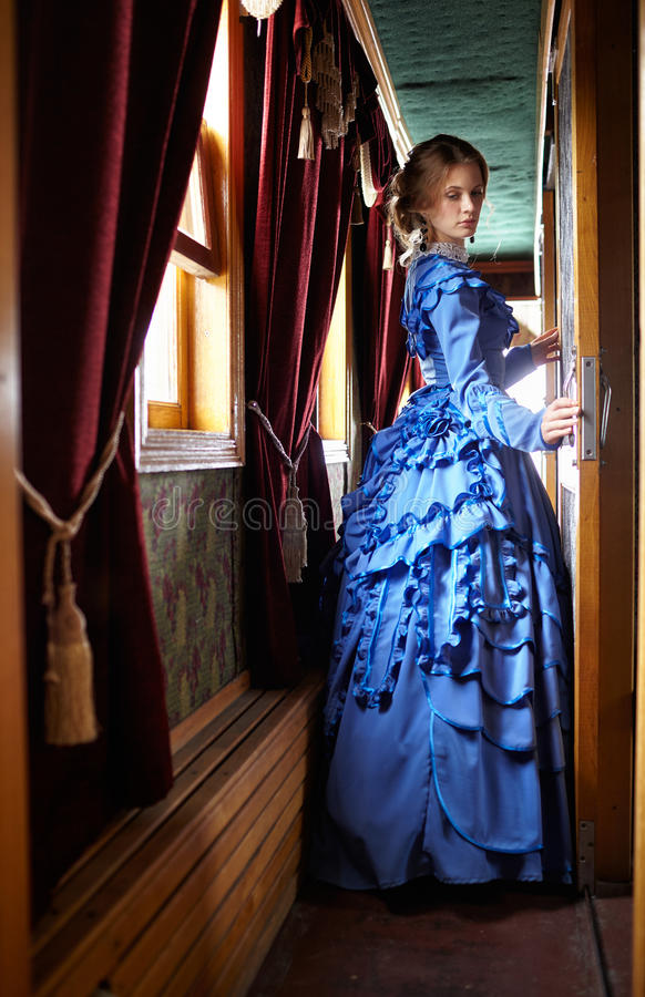 Junge Frau im blauen Weinlesekleid, das im Korridor von Retro- steht lizenzfreie stockfotos