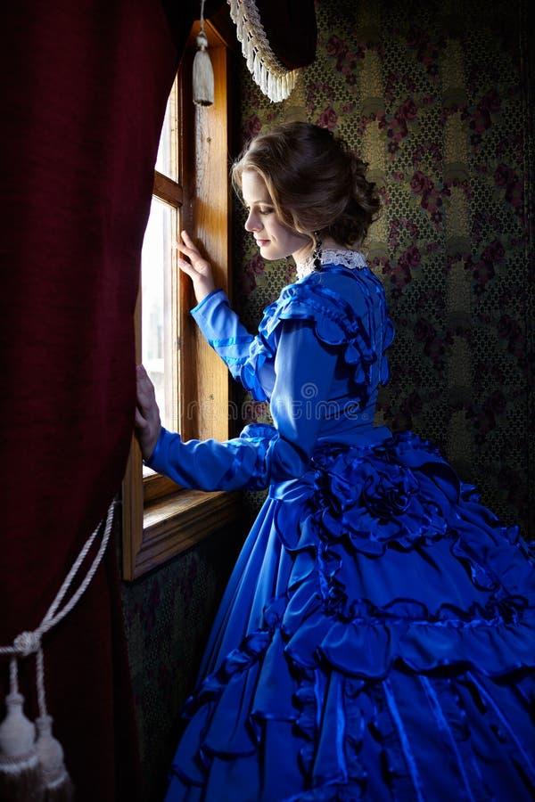 Junge Frau im blauen Weinlesekleid, das nahes Fenster im Coupé steht stockbilder