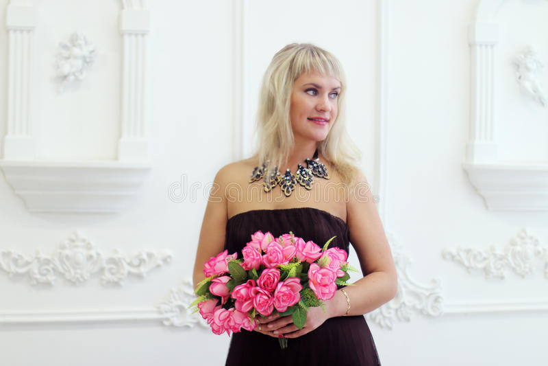 Junge Frau im braunen Kleid hält Blumen stockfotos