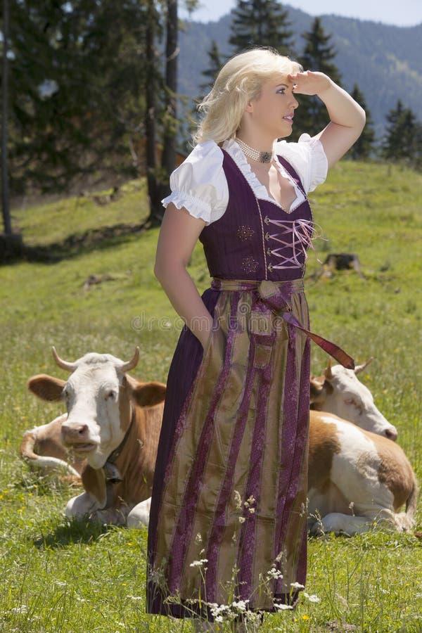 Junge Frau im Dirndl auf dem Bauernhof stockbild