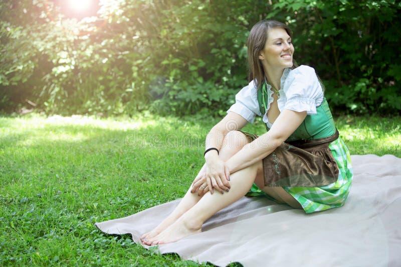 Junge Frau im Dirndl, der auf Decke im Gras sitzt stockbild