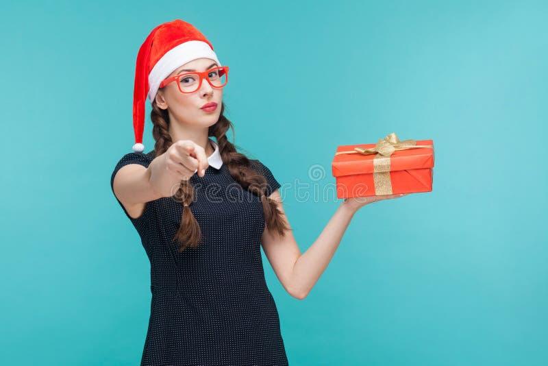 Junge Frau im dunklen Kleid und in den Gläsern, die Geschenkbox halten lizenzfreie stockbilder
