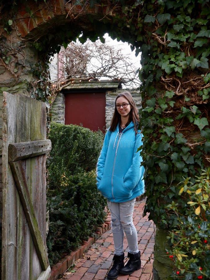 Junge Frau im Eingang des rustikalen Hofes stockbilder