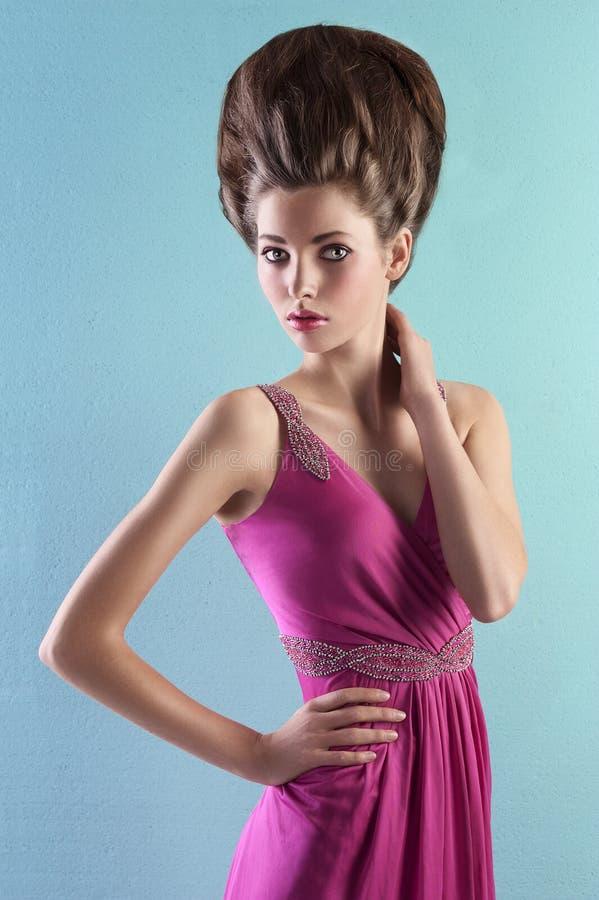 Junge Frau im eleganten rosafarbenen Kleid stockbilder