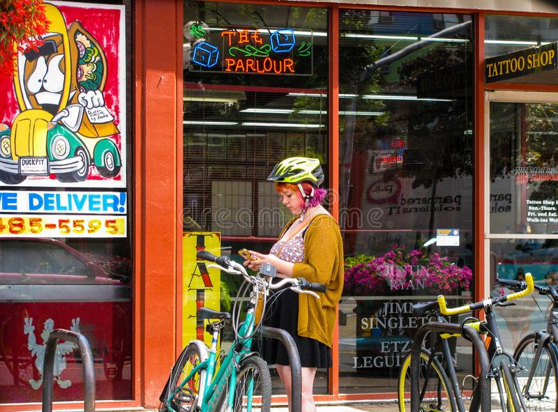 Junge Frau im Fahrradsturzhelm ?berpr?ft Mobiltelefon auf im Stadtzentrum gelegener Stra?e stockbilder