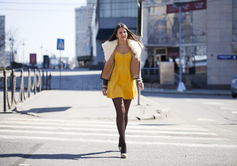 Junge Frau im gelben Kleid, welches draußen die Straße kreuzt stockfoto