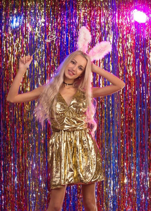 Junge Frau im Goldkleid mit dem blonden Haar stockbilder