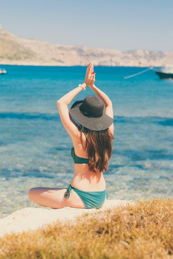 Junge Frau im grünen Badeanzug und im schwarzen Hut übt Yoga auf dem Strand des Mittelmeeres Qigong und Freiheit lizenzfreies stockbild
