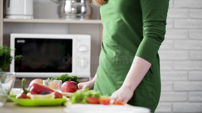 Junge Frau im grünen Kleid, das nahen Küchentisch steht, trägt, Bioprodukte Früchte stockfoto