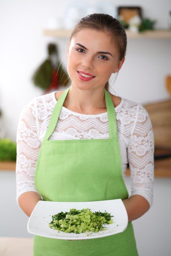 Junge Frau im grünen Schutzblech kocht in einer Küche Hausfrau bietet frischen Salat an lizenzfreie stockfotografie
