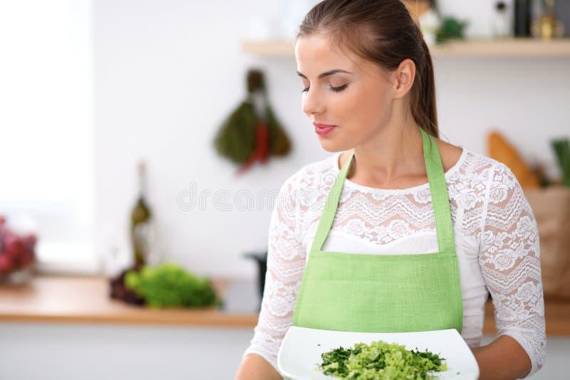 Junge Frau im grünen Schutzblech kocht in einer Küche Hausfrau bietet frischen Salat an lizenzfreies stockbild
