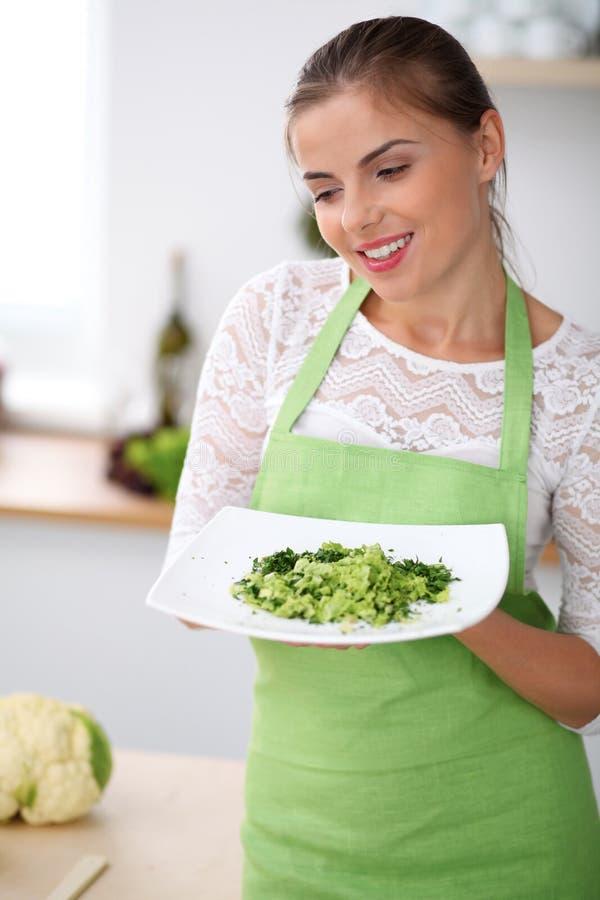Junge Frau im grünen Schutzblech kocht in einer Küche Hausfrau bietet frischen Salat an lizenzfreie stockfotos