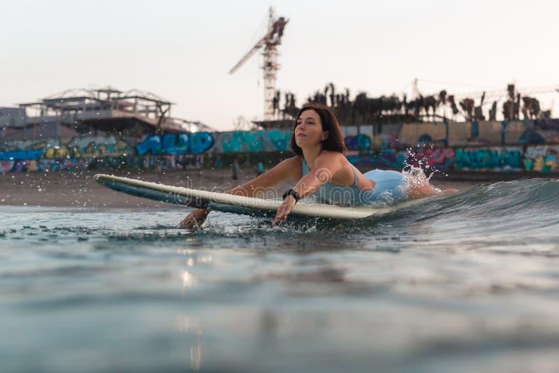 Junge Frau im hellen Bikini, der auf ein Brett im Ozean surft stockfoto