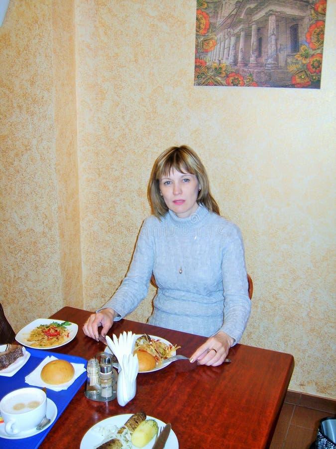 Junge Frau im hellen Haar des Strickkleids, das in einem Café sitzt stockbild