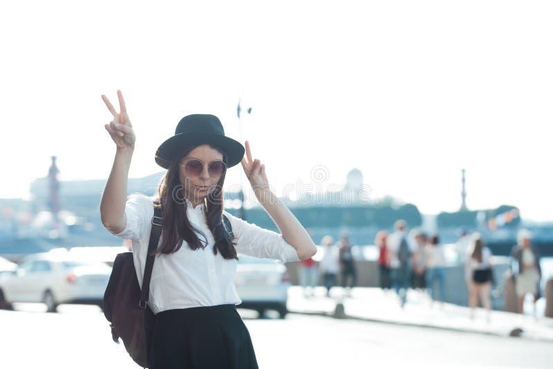 Junge Frau im Hut und in der runden Sonnenbrille gehend in Stadt Mädchentourist genießt den Weg lizenzfreies stockbild