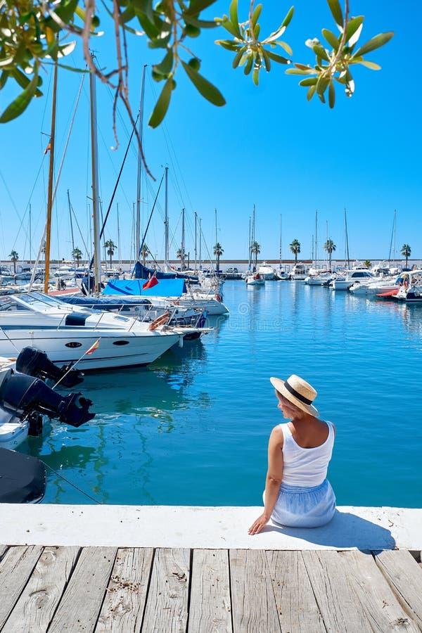 Junge Frau im Hut und netter Sommer kleiden auf dem Pier an Segelboothafen stockfoto