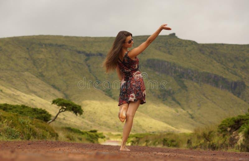 Junge Frau im Kleid mit angehobenem Hand-neare einzelnem Baum auf der Straße stockfotos