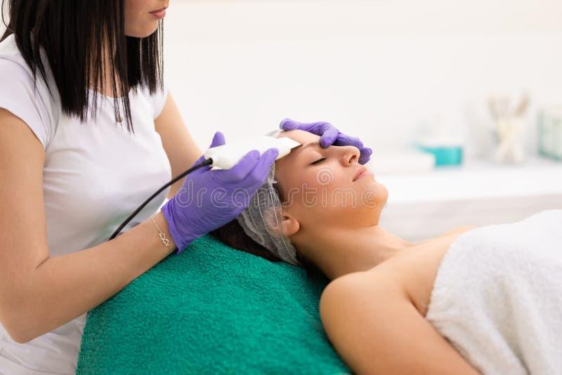 Junge Frau im kosmetischen Salon in Ultraschallhohlraumbildungsbehandlung stockfotos