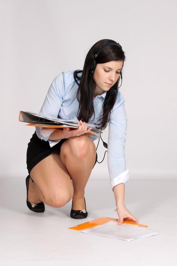 Junge Frau im Minirock und in der Bluse, hockend steigt vom g lizenzfreie stockfotos