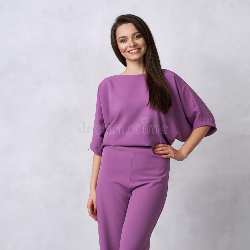 Junge Frau im modernen purpurroten Overall stockbilder