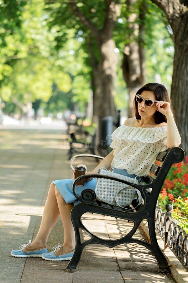 Junge Frau im Park auf trinkendem Kaffee der Bank lizenzfreie stockfotos