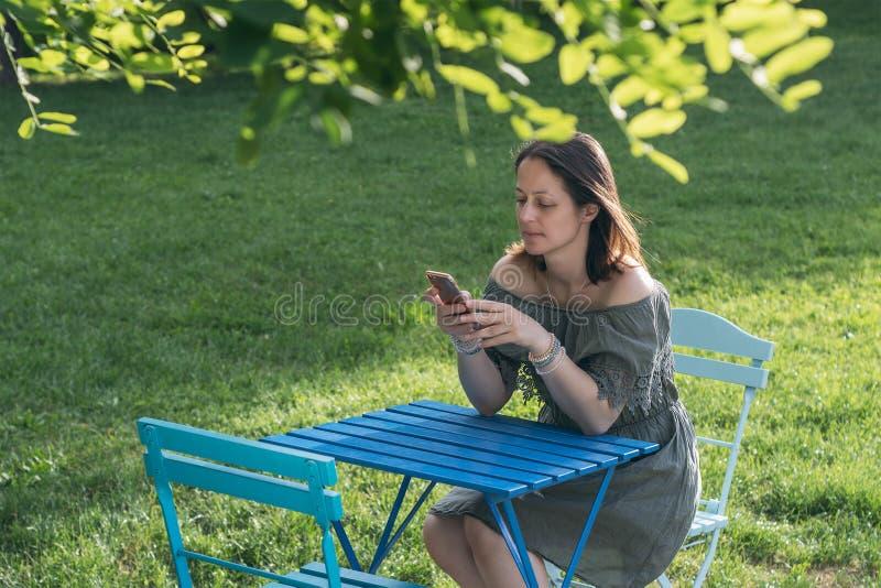 Junge Frau im Park unter Verwendung des Telefons lizenzfreies stockbild