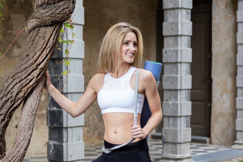 Junge Frau im Pullunder mit Yogamatte stockbild