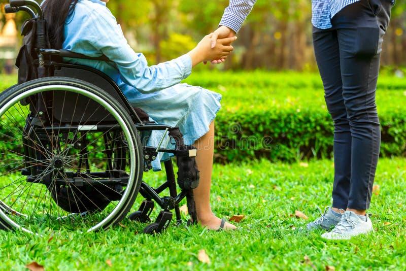 Junge Frau im Rollstuhlhändchenhalten mit Park des Wärtermannes öffentlich lizenzfreies stockbild